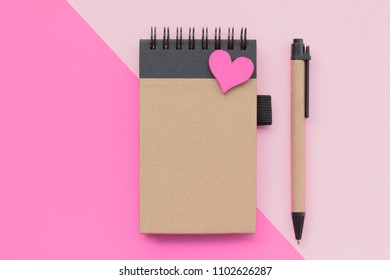Top view flat lay picture with notepad as mockup for your design and different accessories on pink background.
