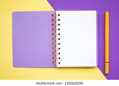Top view flat lay picture with notepad as mockup for your design and different accessories on yellow and violet background.
