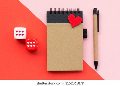 Top view flat lay picture with notepad as mockup for your design and different accessories on red background. Rolling the dice concept for business risk, love, chance, credit, good luck or gambling.