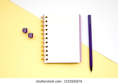 Top view flat lay picture with notepad as mockup for your design and different accessories on yellow background. Rolling the dice concept for business risk, chance, credit, good luck or gambling.