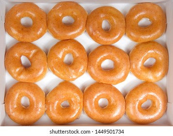 Top view flat lay of plain glazed donuts in a white box isolated. One dozen donuts. The original glazed donut has remained peoples favorite throughout history.