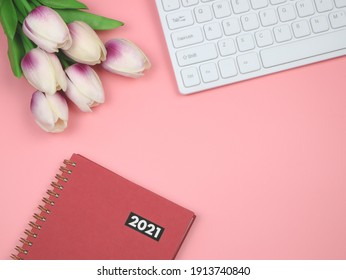 Top view or flat lay of red 2021 diary or planner with computer keyboard, tulip bouquet on pink  blackground with copy space.
