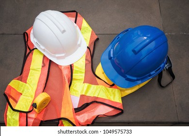 Top view or flat lay of Safety helmet hats, measure tape,  and worker dress on concrete floor at modern city. Engineer and construction equipment with copy space for text.