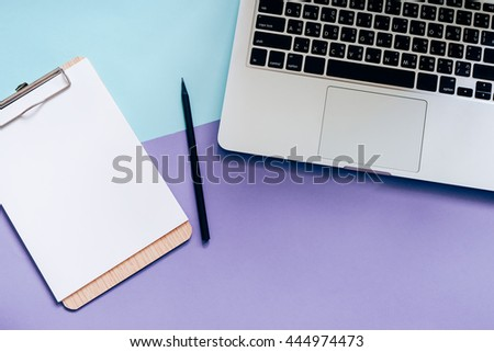 Top view flat lay style of worksapce desk with laptop and blank clipboard on minimal color background