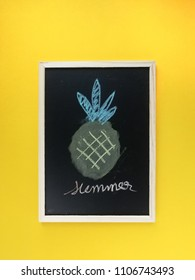Top view flat lay of sweet pineapple with blackbord for Text space on yellow summer background.