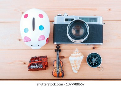 top view flat lay travel concept with retro camera films, compass, plant, piggybank and other miniature on wooden desk