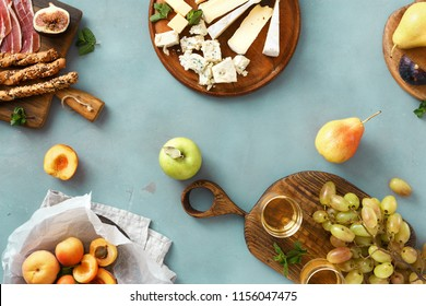 Top view flat lay various wine snacks: grapes, peach, apricot, pear, apples, jamon, hard cheese, brie cheese and roquefort cheese on blue stone background with glass white wine