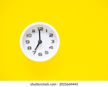 Top view, Flat lay, white clock show time at 7 o'clock on office yellow workplace tabletop. Copy space for your text. Business and education concept.