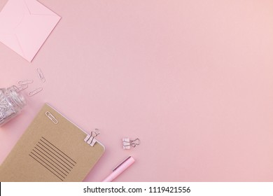 Top view flat lay of woman workspace desk styled design office supplies with copy space on a millennial pink color paper background minimal style. Template for feminine blog social media