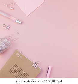 Top view flat lay of woman workspace desk styled design office supplies with copy space on a millennial pink color paper background minimal style. Square Template for feminine blog social media