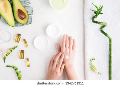 Top view and flat lay of woman puts cream on hands over white table with cosmetic products - avocado oil, cream and bamboo. Bod ycare concept