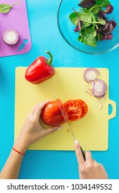 Top view, flat lay womens hands cooking salad on blue surface