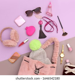 Top view, flat lay women's fashion accessories concept image of bag, makeup tools, necklace, perfume, sun glasses, beret, hand mirror, lipstick, purse on lilac and sand stone background