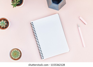 Top view flat lay of workspace desk styled design office supplies and cactuses succulents with copy space millennial pink color paper background minimal style. Template for feminine blog social media