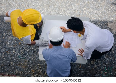 Top view or flat lay of young engineer present constructed blueprint plans to site manager and foreman at construction site. Business Engineering Concept for team work in working place.