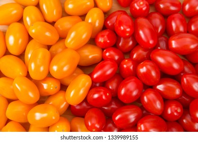 Top view flat lay of Zima, an orange grape tomatoes next to Angel Sweet grape Tomatoes. Both great for salads or snacking.