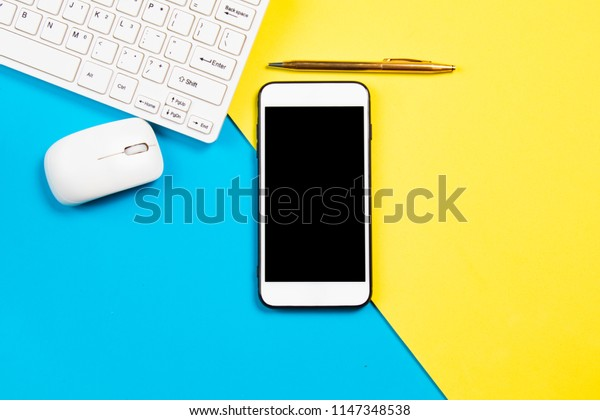 Top view, flat ray, of business desk composite with smartphone, keyboard, mouth, and pen on colorful pastel background with copy space/ business concept