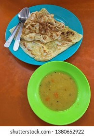 Top view of flatbread Roti canai, also known as Roti cane, Roti parotta served with dal on wooden table