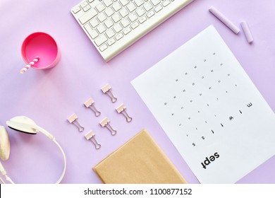 Top view flatlay composition of girly lifestyle items on pastel purple background, computer keyboard, pink milkshake or smoothie and calendar sheet for September on desk in office, copy space