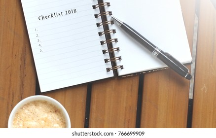 Top view or flatlay of notebook with words Checklist 2018 and blank checklist on rustic wooden table with pen and mug of coffee