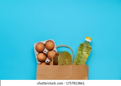 Top view, flatlay. Set of products inside paper bag on the blue background. Packaging food from the store. Sunflower oil, eggs, canned food. Delivery and donation concept