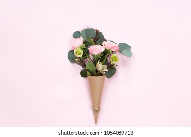Top view of floral composition of beautiful pink rose flower in kraft cornet on white background, flat lay, copyspace