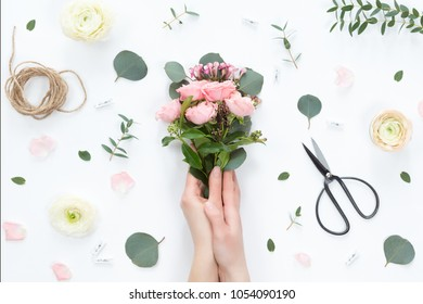 Top view of floral composition of beautiful pink rose flower bouquet on white background with leaves, florist shears, jute rope, flat lay, copyspace