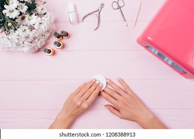 Top view floral composition female hands remove sticky layer from gel nail polish. Flat lay arrangement woman making shellac manicure herself near UV lamp, tools and bouquet of flowers on pink table.