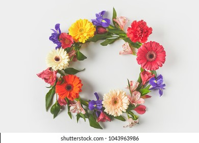 top view of floral wreath made of beautiful colorful flowers and green leaves on grey