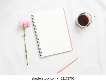 Top view of flower and  blank notebook on white fabric workspace background.