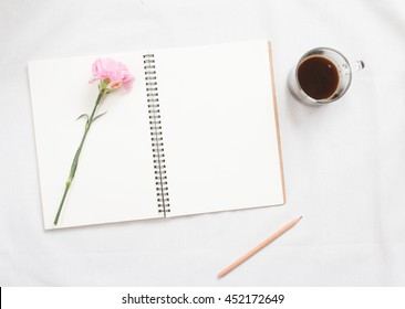 Top view of flower on blank notebook on white fabric workspace background.