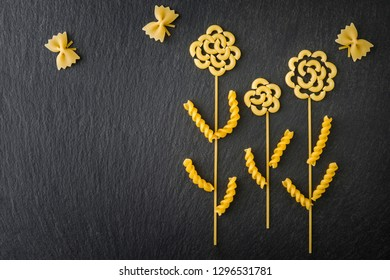 Top view flowers and butterflies made out of various pasta on the dark slate background.