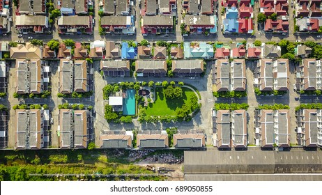 Top view flying over townhome showing neighborhood family houses real estate with roofs, swimming pool and gardens.