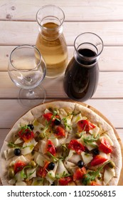 Top view focaccia with cheese, tomato and olives and two pitchers with red and white wine