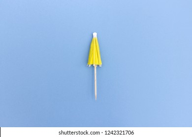 Top view of folded cocktail umbrella in yellow color on blue background