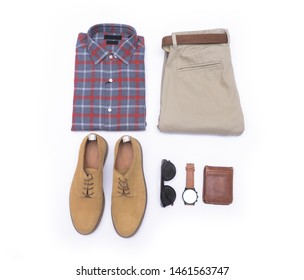 Top view of folded long sleeve plaid shirt and khaki pants ,watch with belt and brown shoes ,sunglasses,purse on white background