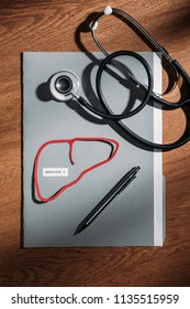 top view of folder, stethoscope, and liver with lettering hepatitis c on table, world hepatitis day concept