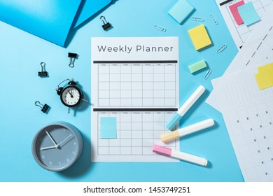Top view of folders, alarm clocks, colorful stationery and weekly planner on pastel blue background