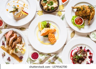 Top view of food assortment. Luxury buffet flat lay. Selection of plates and dishes on white background