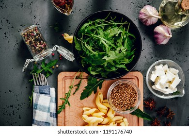 Top view of food ingredients, rucola, garlic, dried tomatoes in brine, pasta, feta cheese. The concept of preparing dishes with pasta and rucola on a stone counter top. Food photography.