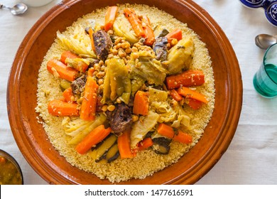 Top view food shot of a typical moroccan couscous served on a family size ceramics tagine plate surrounded by glasses, sauce, spoons and spices on a fine linens background. Blessed friday concept.