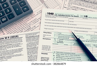 top view of forms for usa taxes, with a pen and an electronic calculator (3d render)