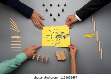 Top view of four business people assembling yellow light bulb with puzzle pieces with various elements of business start up on grey desk.