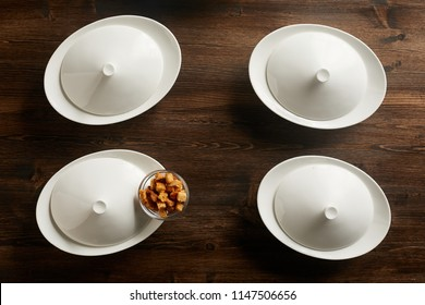 Top view of four closed soup bowls with rusks