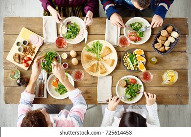 Top view of four people eating at festive dinner table with delicious food in cafe or restaurant
