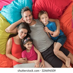 top view of a four people family laying on their sofa with large cushions. They are cuddling, the grey hair father is hugging his wife and his blond son and the mother is holding her daughter