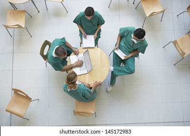 Top view of four physicians in meeting with reports and laptop at the cafeteria