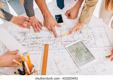 Top view of four successful architect reviewing blueprints and using a digital tablet. Close-up.