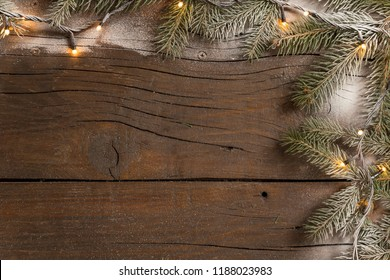 Top view of a frame made of snowy pine branches and Christmas lights placed on wooden table