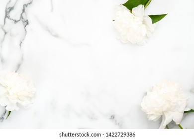 Top view frame of white peony flowers on marble background. Minimal flat lay style home desk with peonies. Wedding invitation card mockup with copy space. Beauty or fashion blog banner template